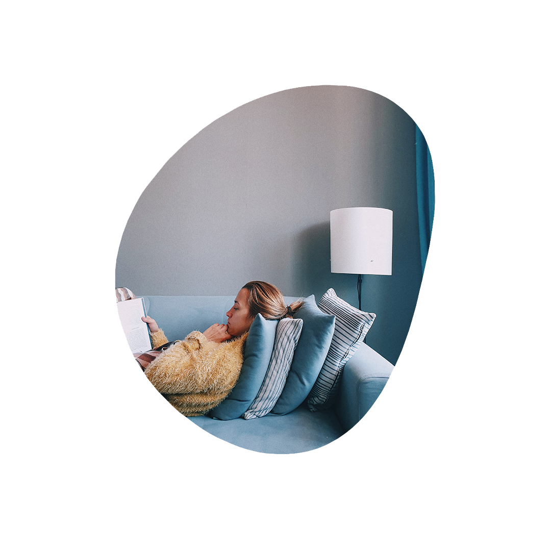 Woman reading book on couch. Lots of blue tones and white lamp.