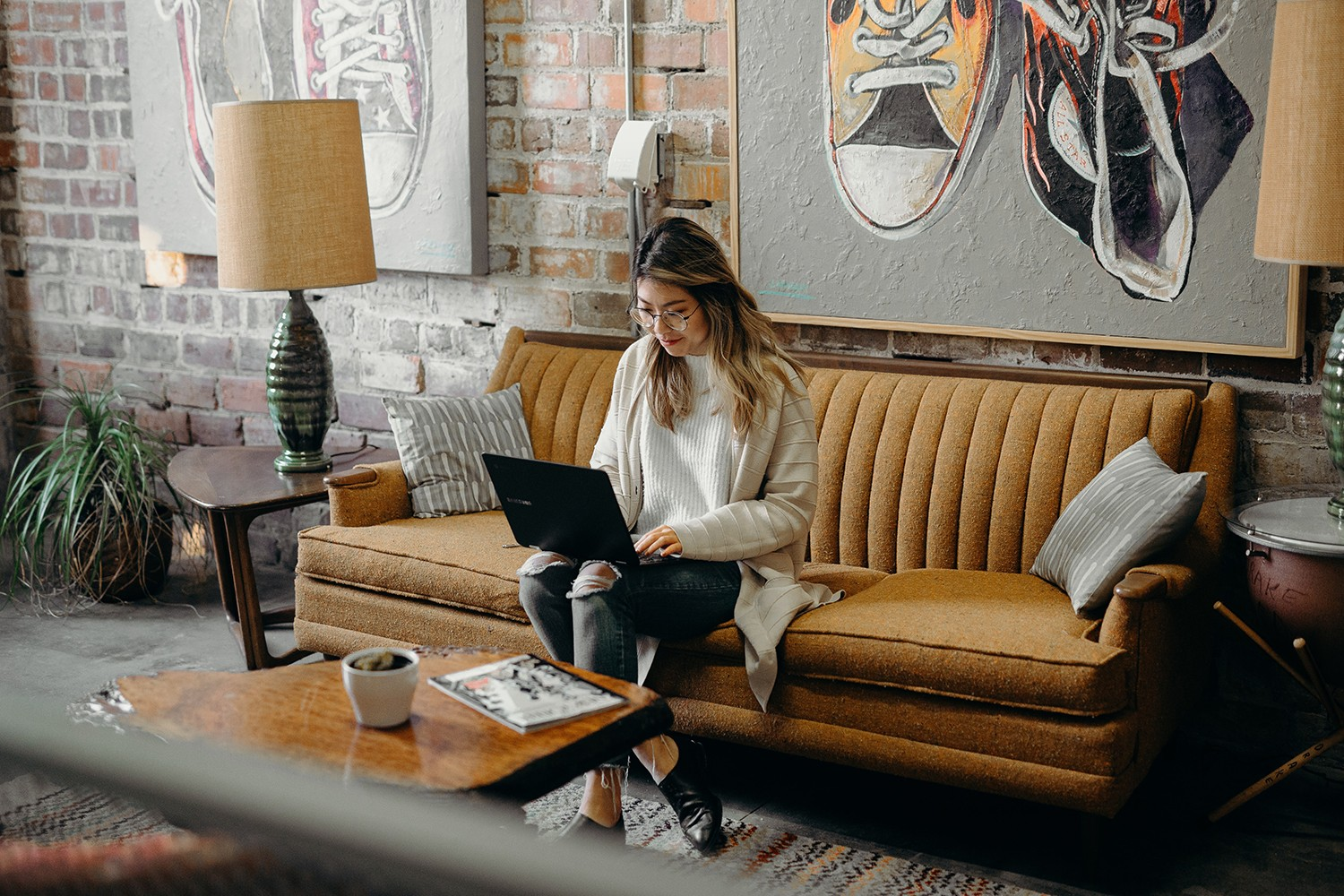 Woman working from cafe on mustard couch and large coffee on the coffee table in front of her.