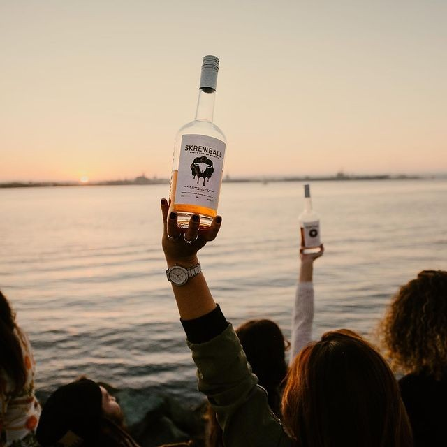Wine Bottle held in partygoers hand at the ocean during sunset.