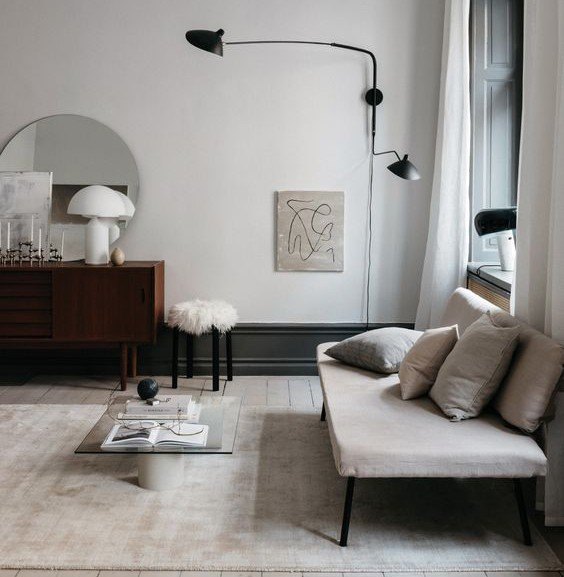 Modern grey and white living room with circular mirror and dark modern wall mounted lighting.
