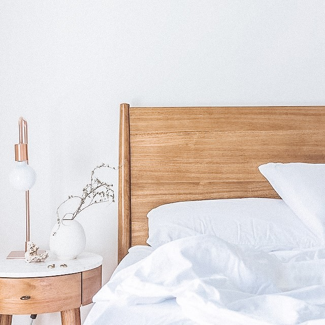 Materials we like. Close up of wooden bed with copper nightlight, white sheets and a blank, white wall.