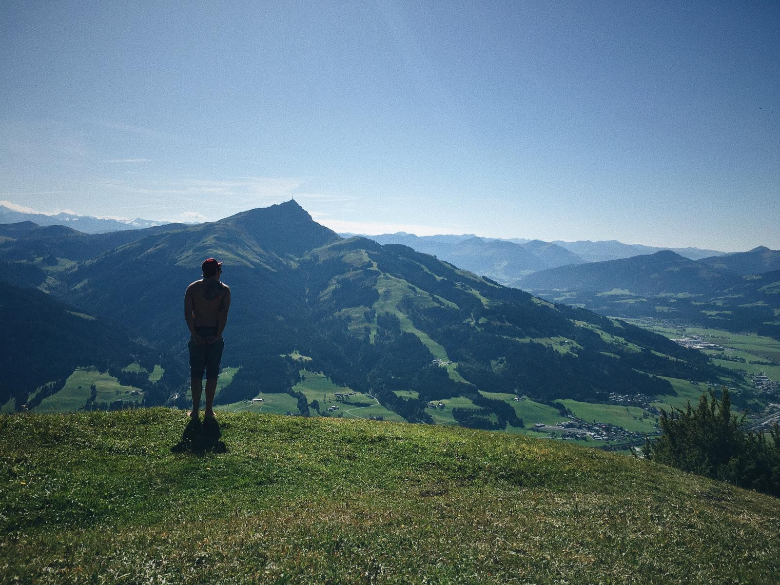 Man standing on mountain top with clear blue sky.